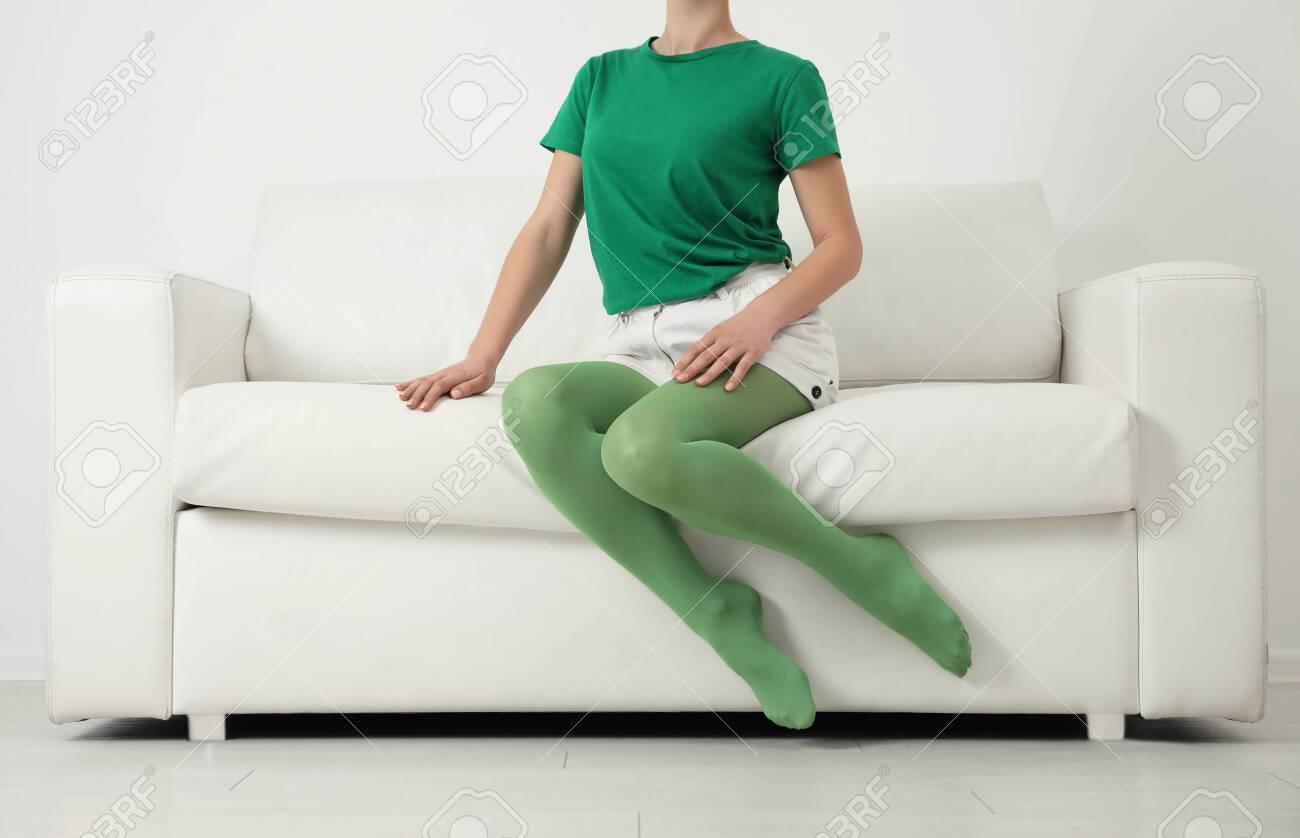 Woman wearing green tights sitting on sofa indoors, closeup - 136628768