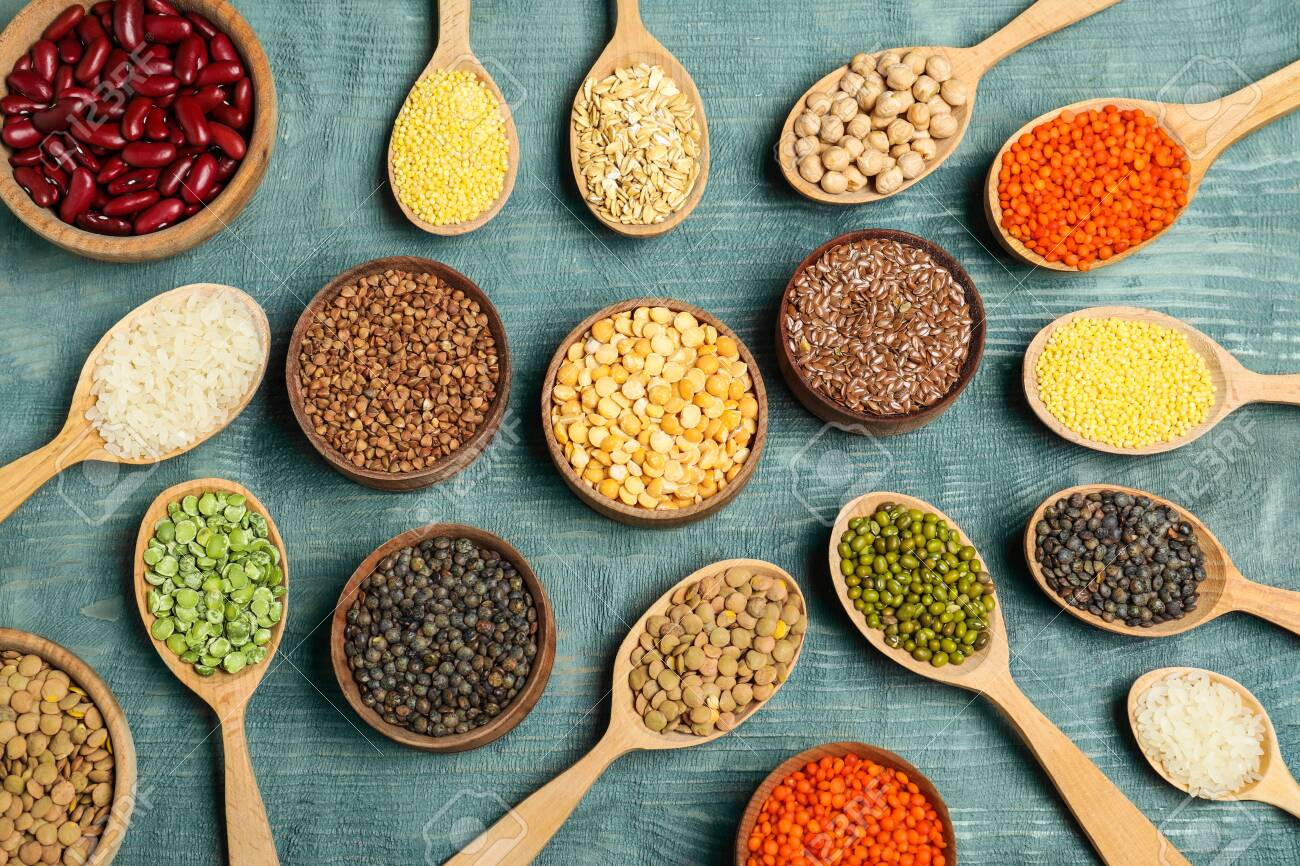 Flat lay composition with different types of legumes and cereals on blue wooden table. Organic grains - 136862890
