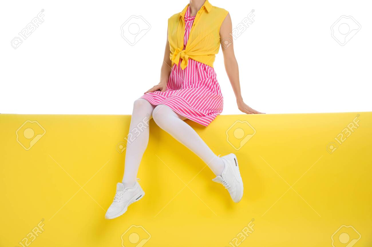 Woman wearing white tights sitting on color background, closeup - 136967930