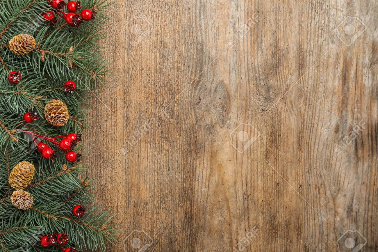 Flat lay composition with fir branches and berries on wooden background, space for text. Winter holidays - 137149323
