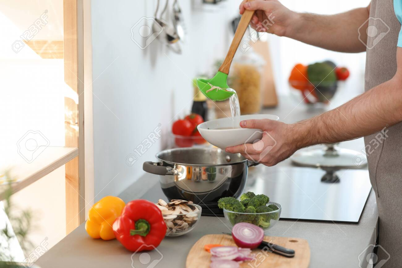 Young man pouring delicious soup into bowl at home, closeup - 137247869