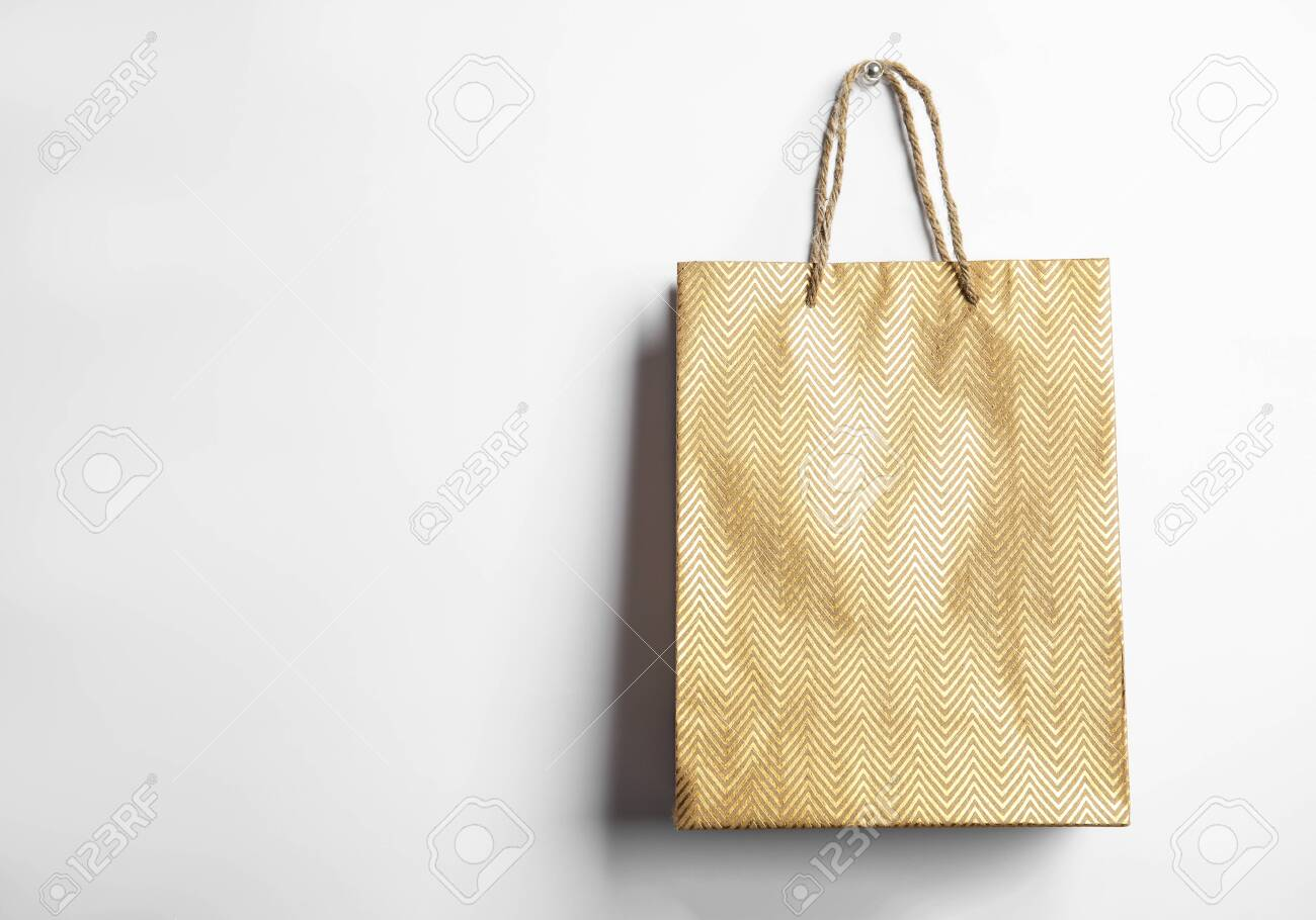 Gold shopping paper bag isolated on white - 137326507