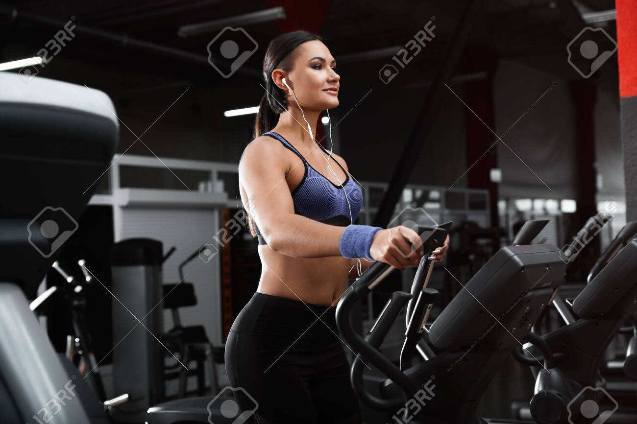 Young woman working out on elliptical trainer in modern gym - 138543826