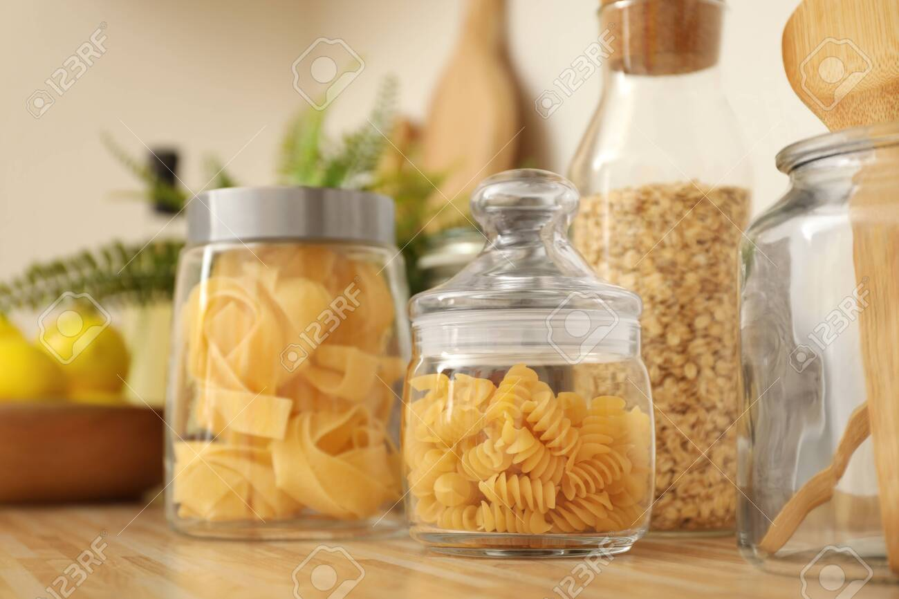 Jars with products on wooden kitchen countertop - 139271107