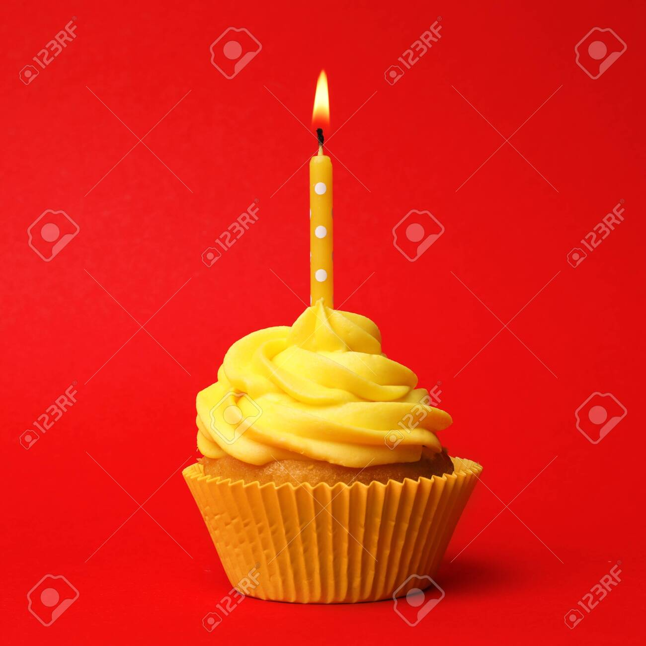 Delicious birthday cupcake with yellow cream and burning candle on red background - 139920398