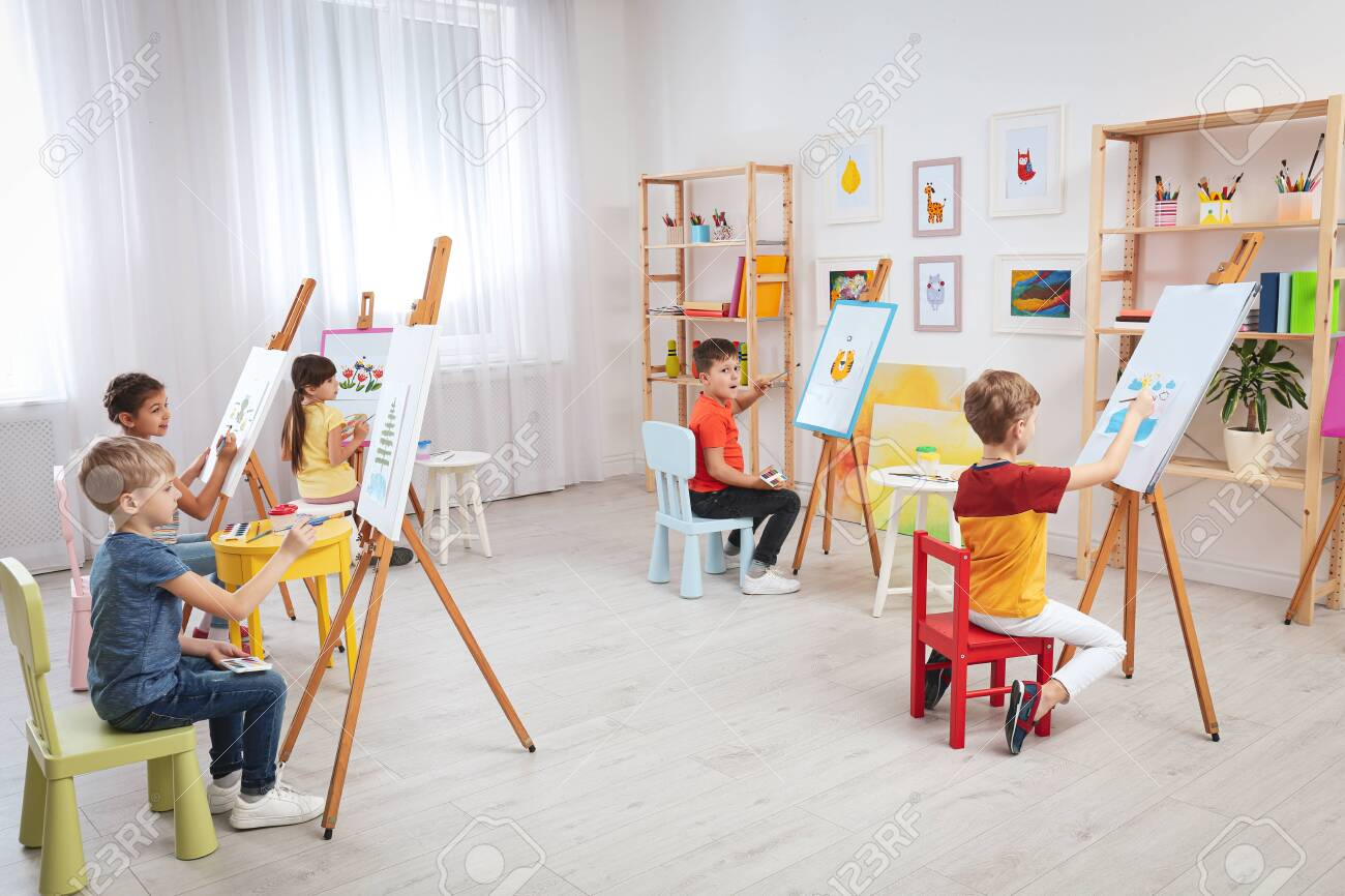 Cute little children painting during lesson in room - 140823265