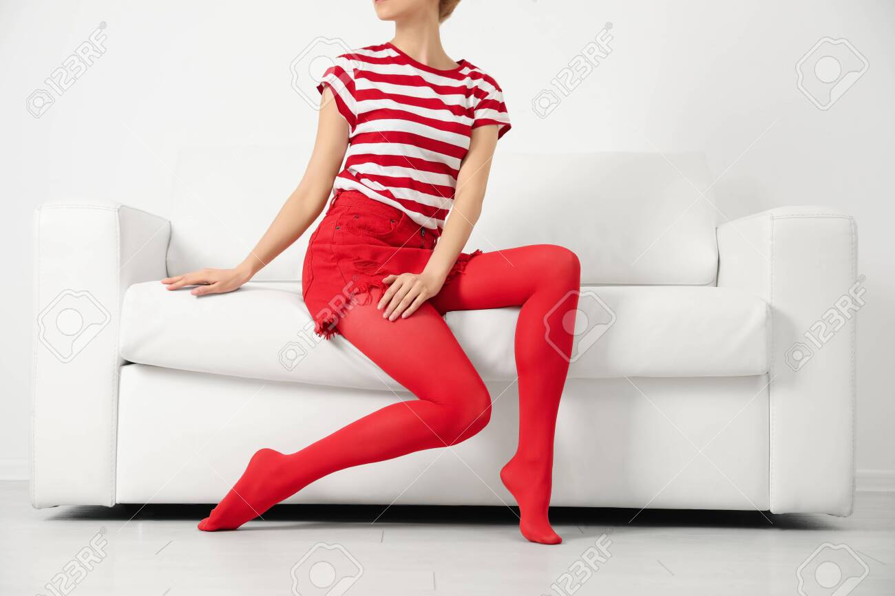 Woman wearing red tights sitting on sofa indoors, closeup - 140107944