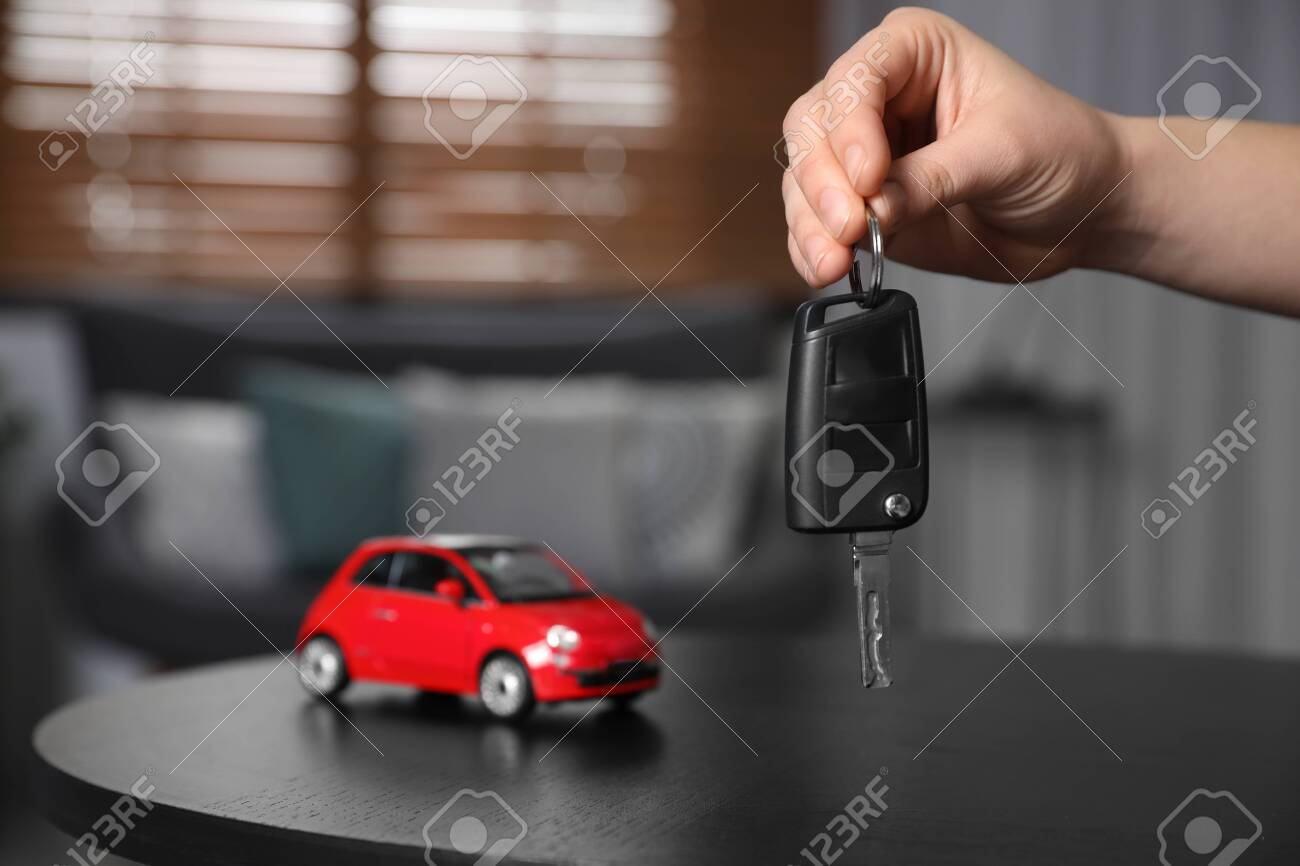 Man holding key near table with miniature automobile model indoors, closeup. Car buying - 140185531