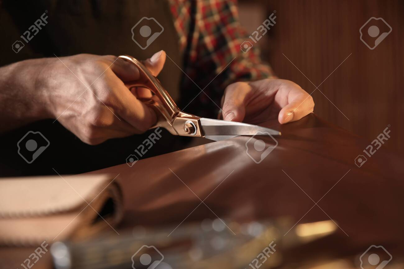 Man cutting leather with scissors in workshop, closeup - 140345545