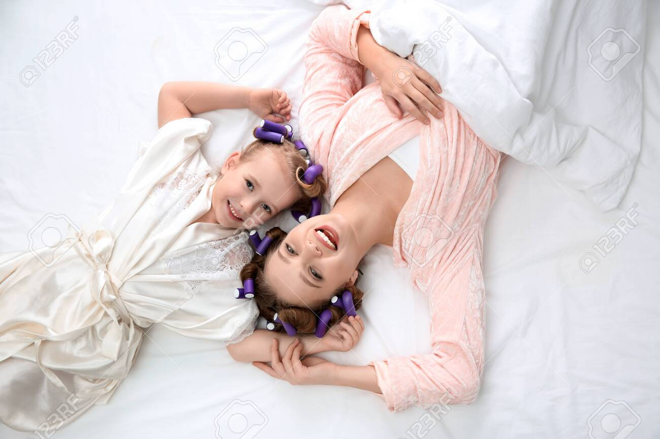 Happy mother and daughter with curlers lying on bed, top view - 140544092