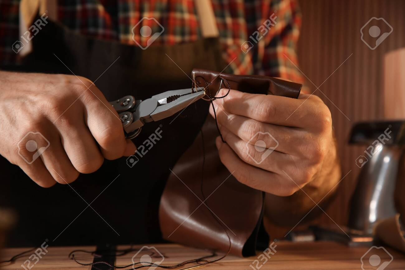 Man sewing piece of leather at table, closeup - 141145376