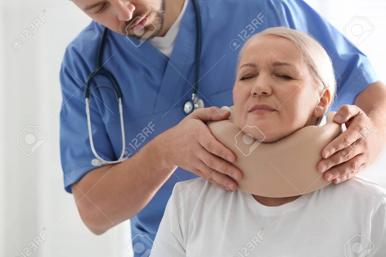 Orthopedist applying cervical collar onto patient's neck in clinic, closeup - 141038052