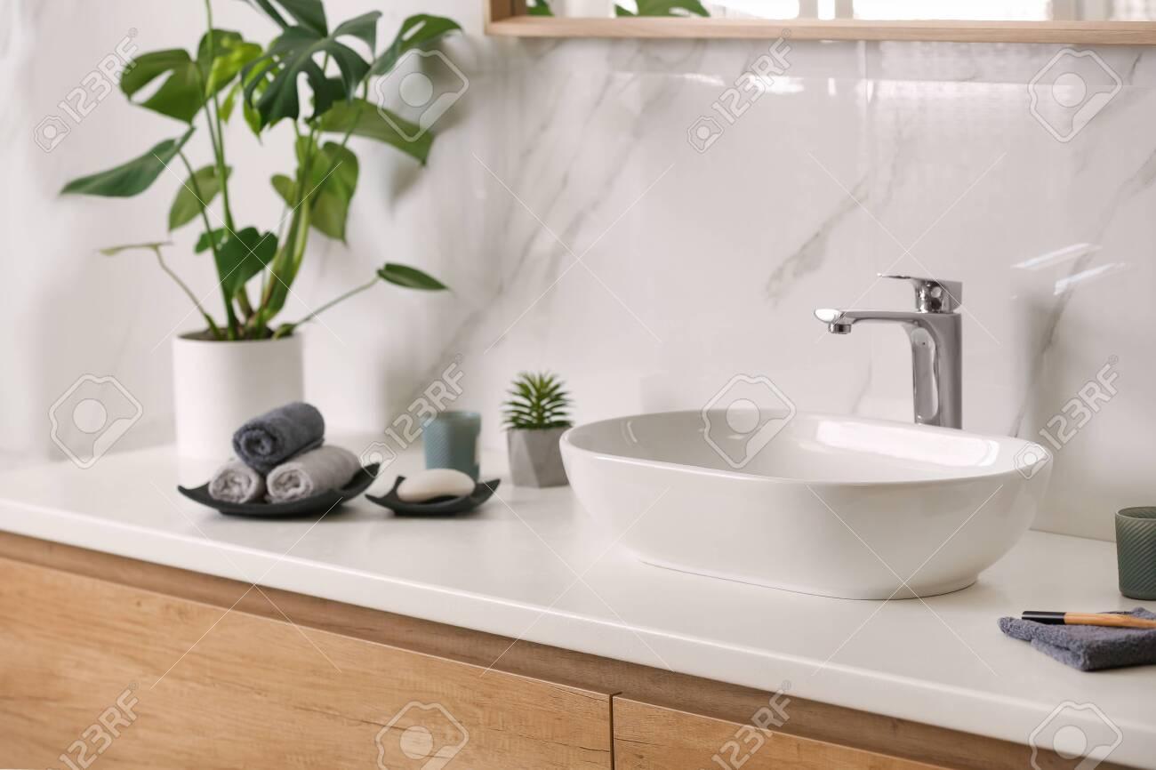 Stylish vessel sink on light countertop in modern bathroom - 141061097