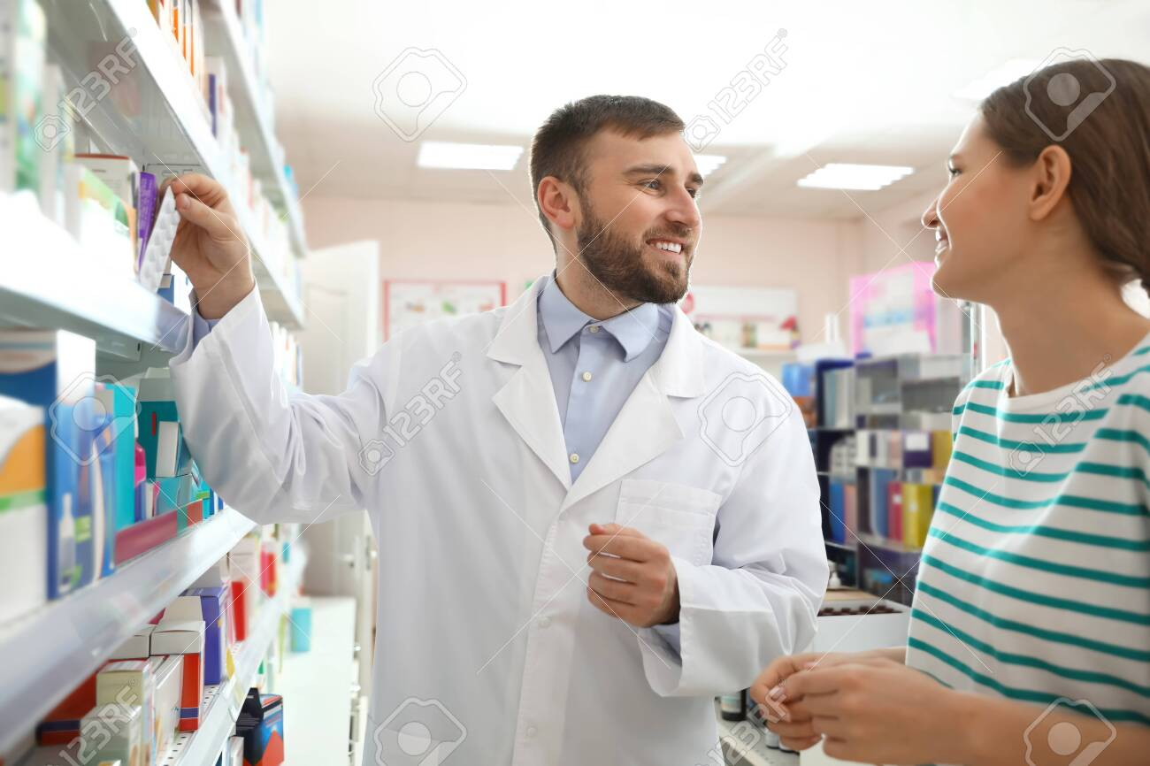 Professional pharmacist working with customer in modern drugstore - 141112001