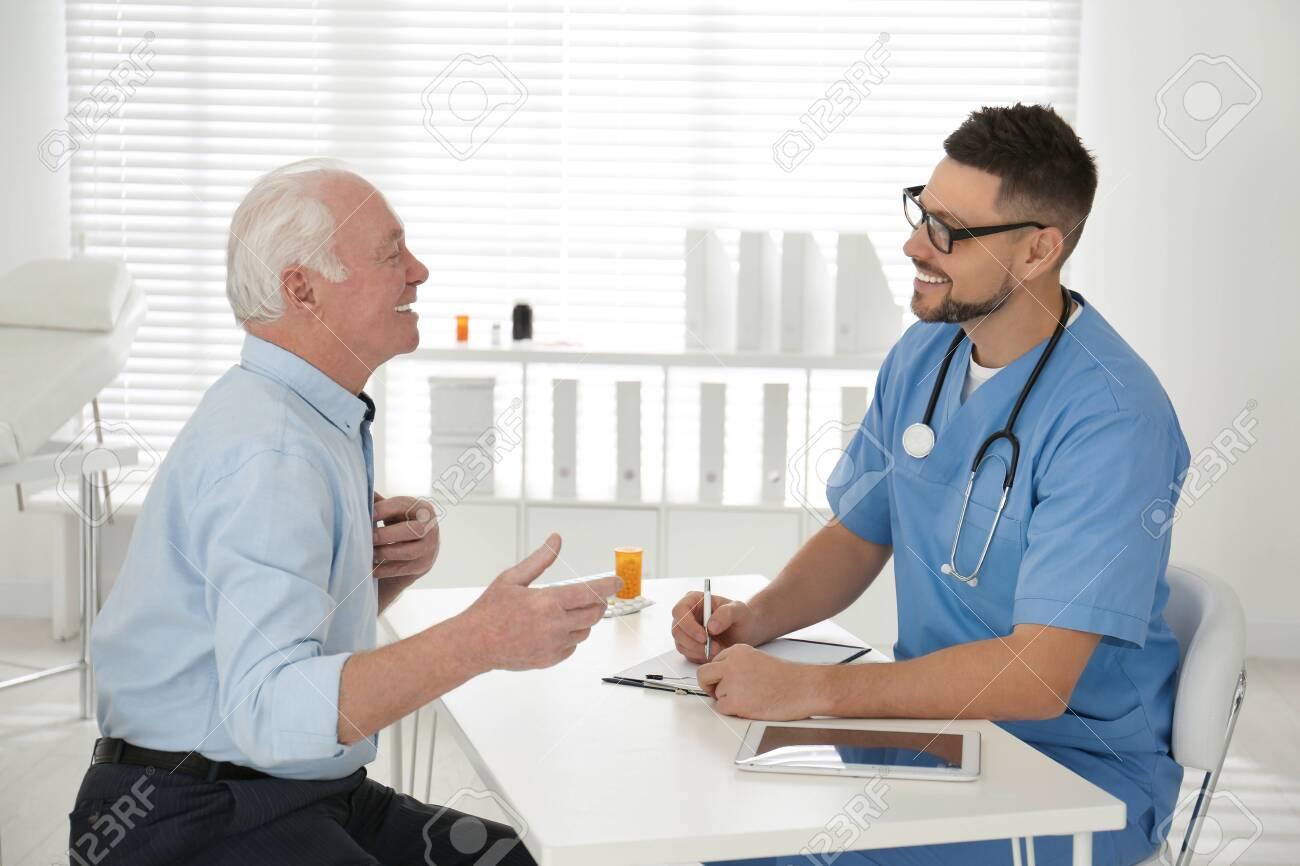 Doctor examining senior patient in modern office - 141985658