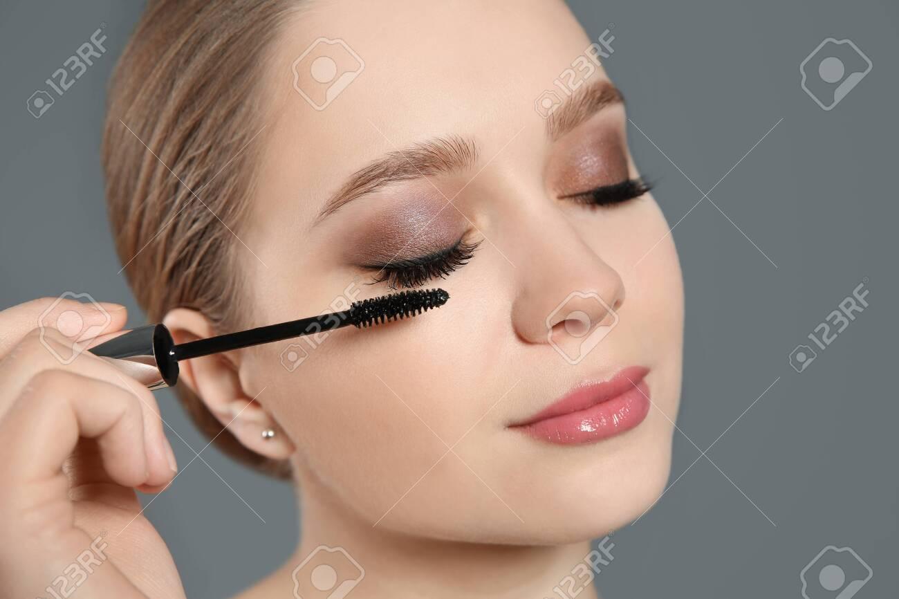 Beautiful woman applying mascara on light grey background. Stylish makeup - 141453756