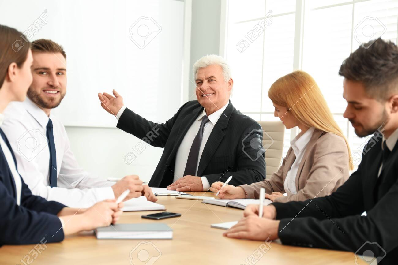 Senior business trainer working with people in office - 141625538