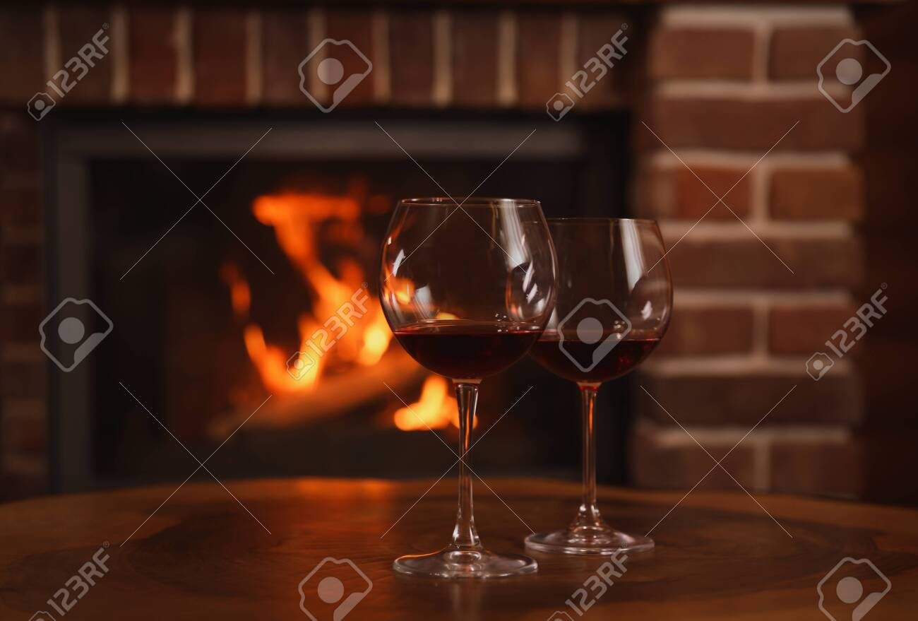 Glasses of red wine on wooden table near fireplace. Space for text - 141674216