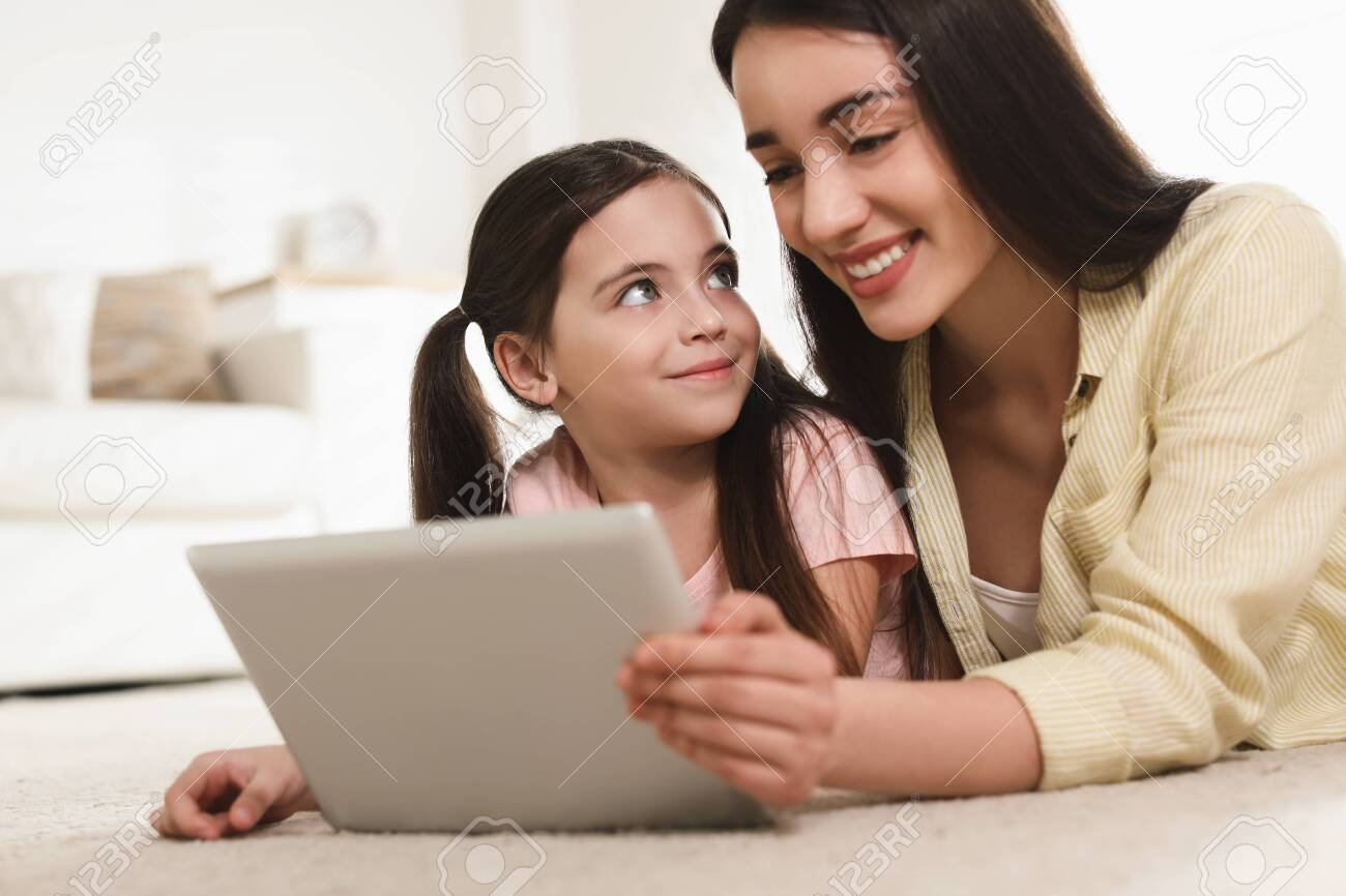 Mother and daughter reading E-book together at home - 141863258