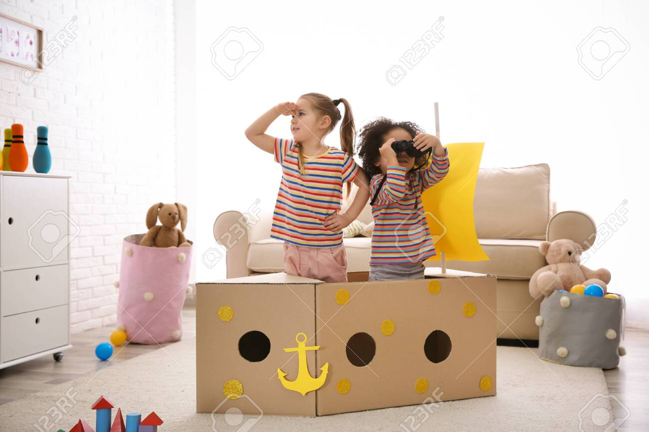 Cute little children playing with cardboard ship and binoculars at home - 142693453