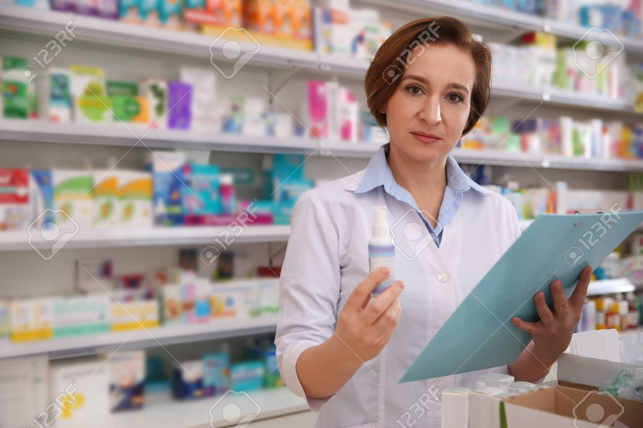 Professional pharmacist with clipboard and medicine in drugstore - 142386378