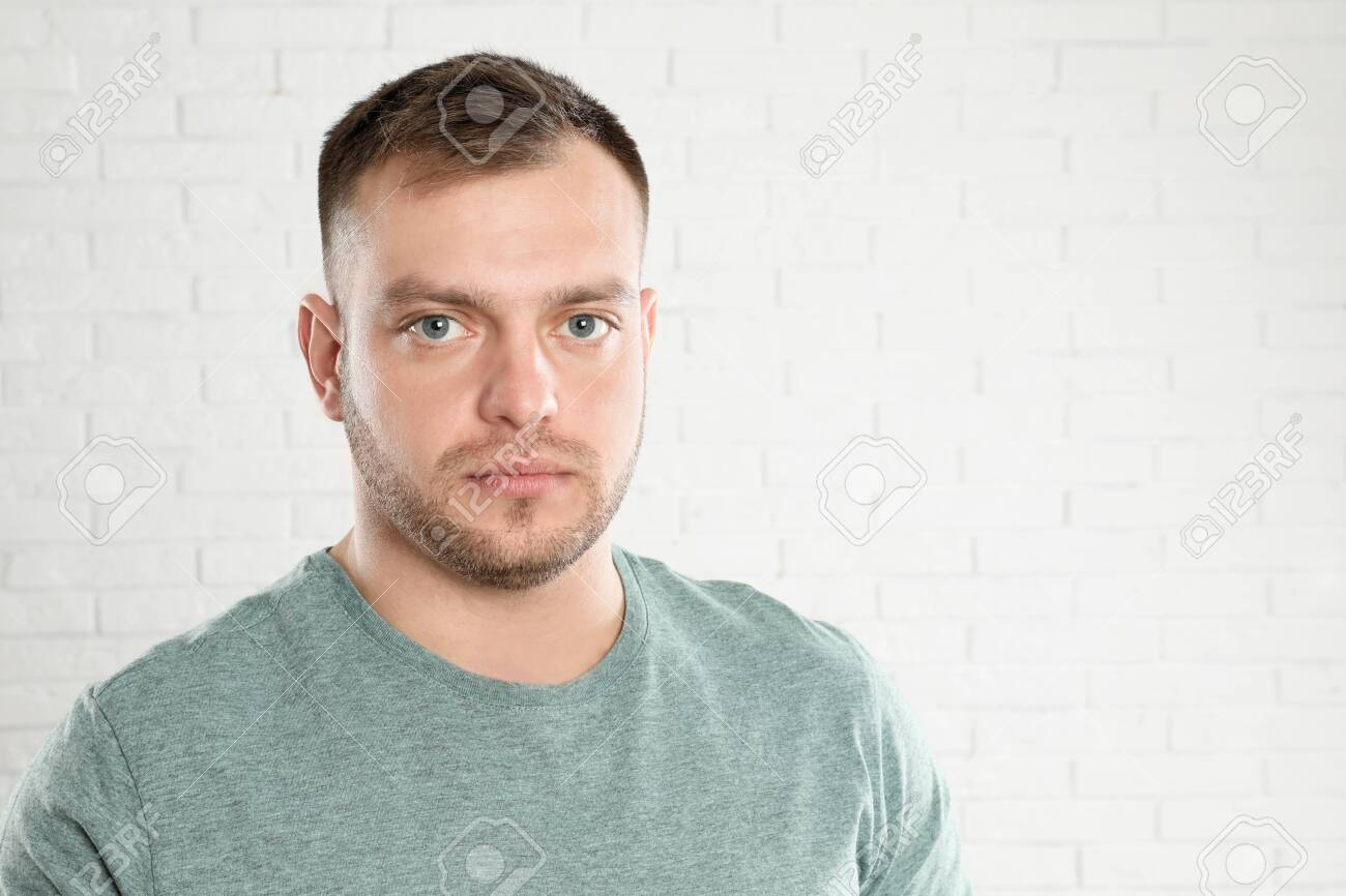 Portrait of young man near white brick wall. Space for text - 142477228