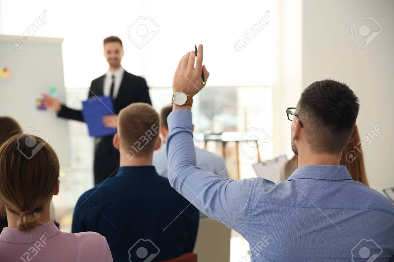 Man raising hand to ask question at business training indoors - 142464435