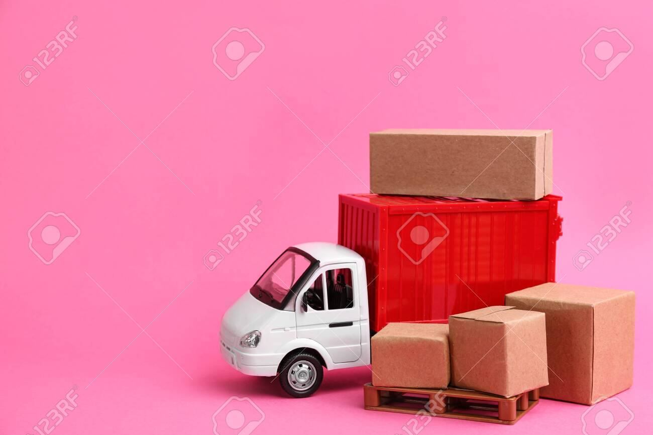 Truck model and carton boxes on pink background, space for text. Courier service - 142280570