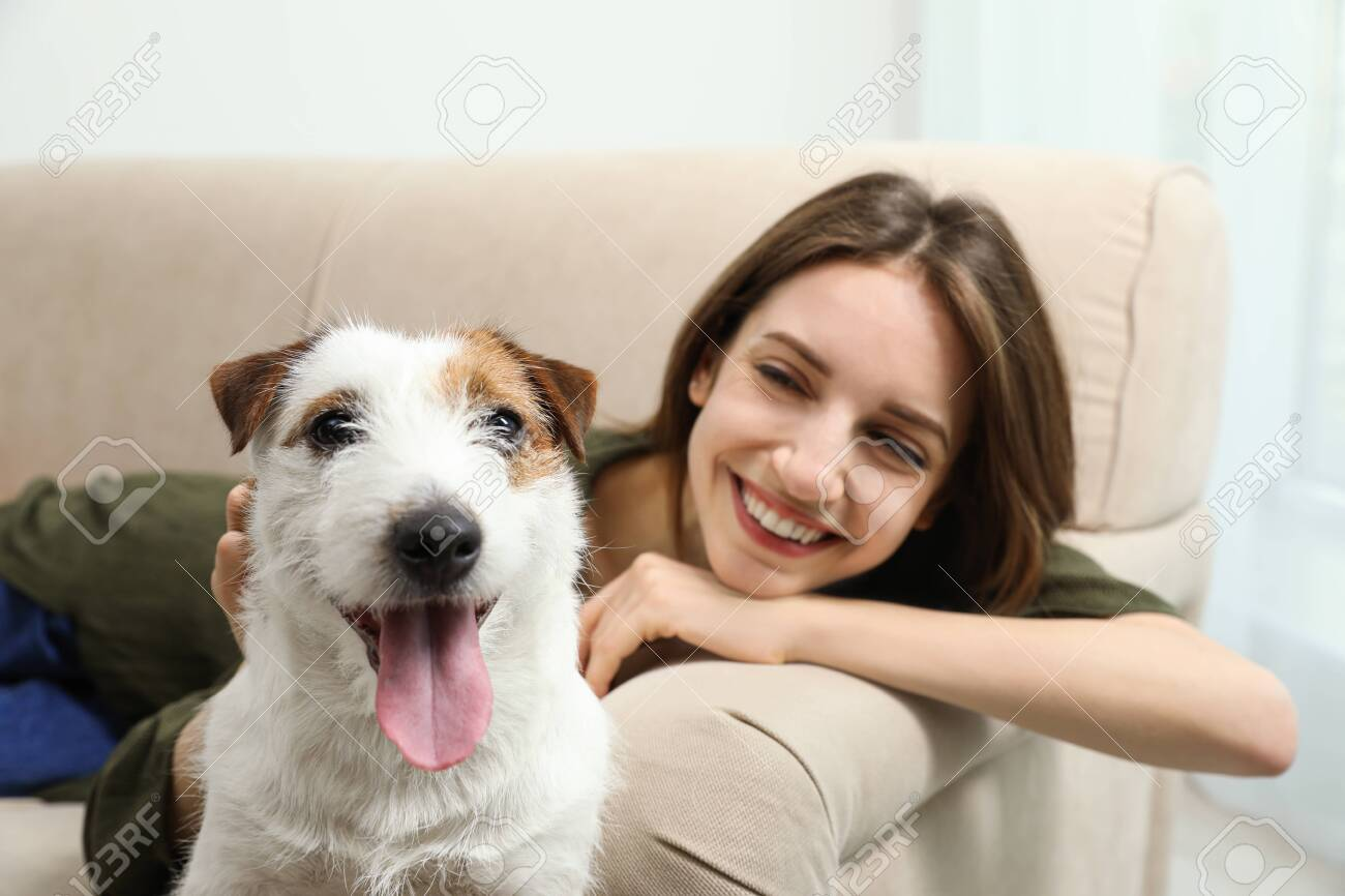 Young woman with her cute Jack Russell Terrier on sofa at home. Lovely pet - 142673980