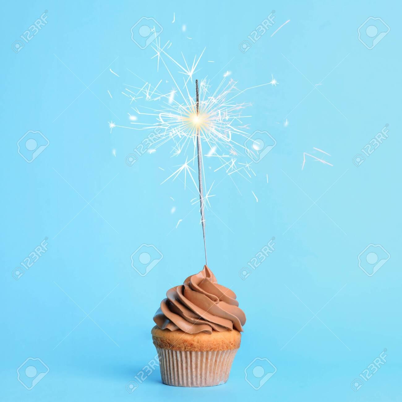 Birthday cupcake with sparkler on light blue background - 142770122