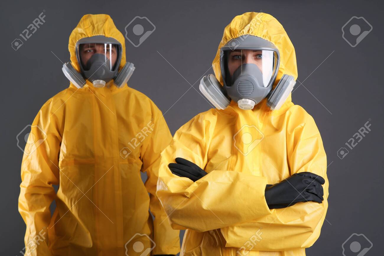 Man and woman wearing chemical protective suits on grey background. Virus research - 142770148
