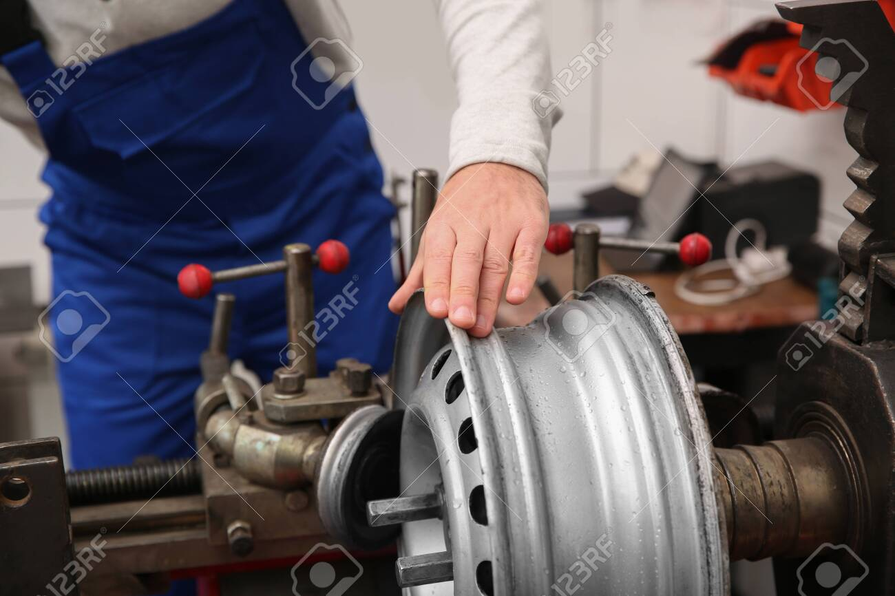 Mechanic working with car disk lathe machine at tire service, closeup - 142846206
