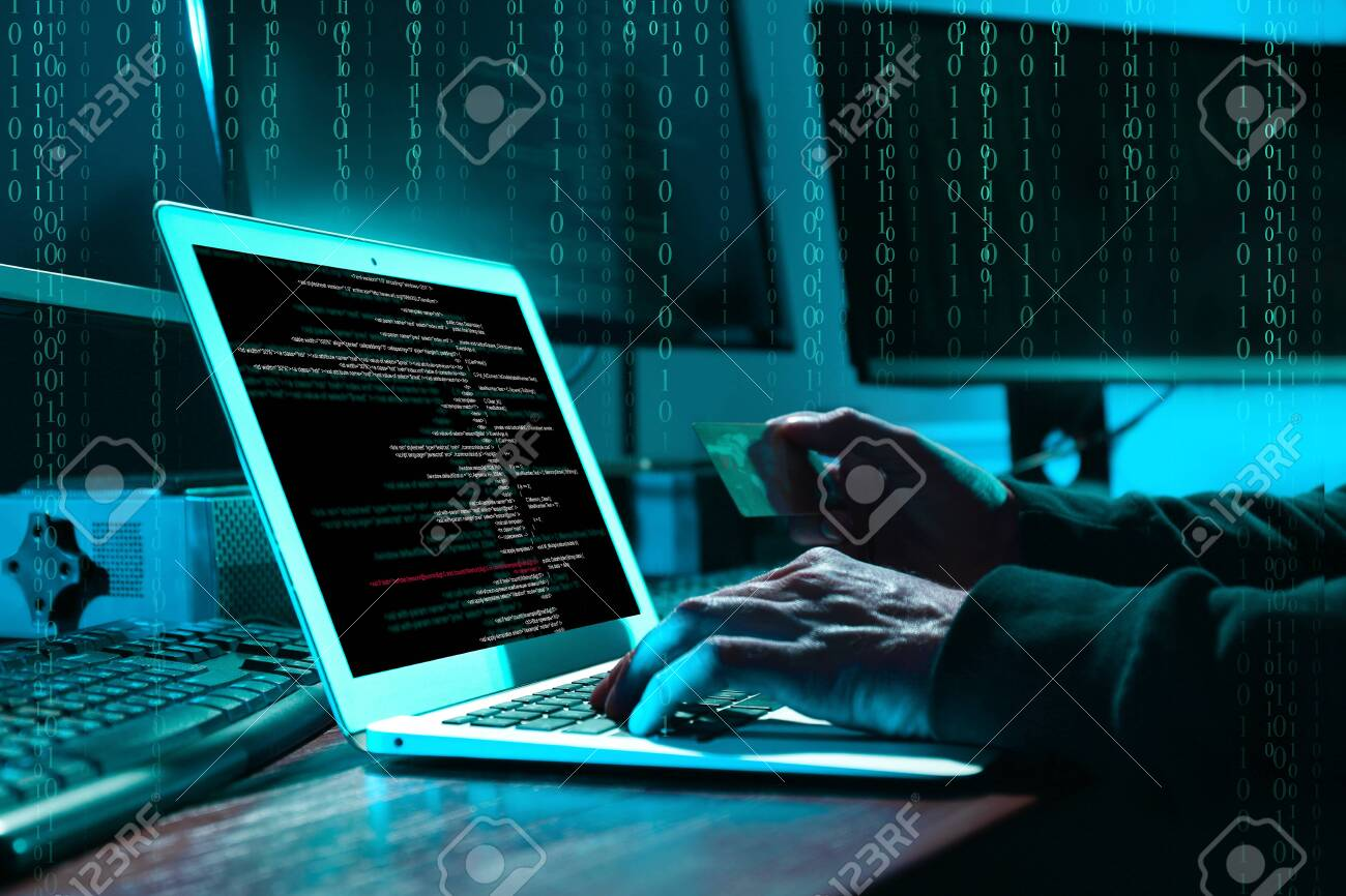 Cyber criminal with credit card hacking system at table, digital binary code on background - 143198616