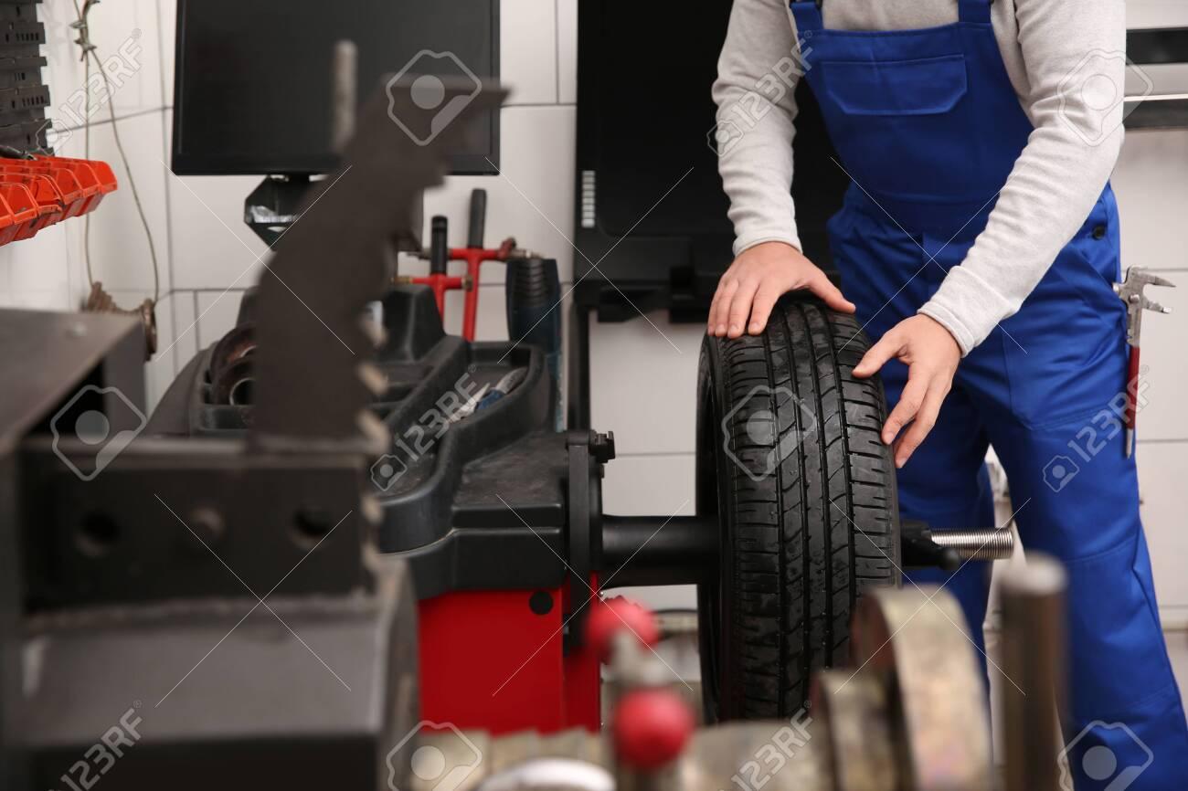 Mechanic working with wheel balancing machine at tire service, closeup - 143487821