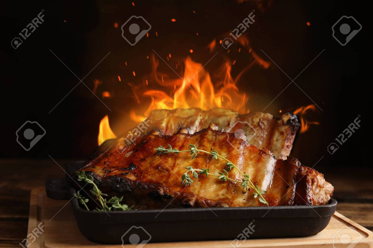 Tasty grilled ribs and flame on wooden board - 144305487