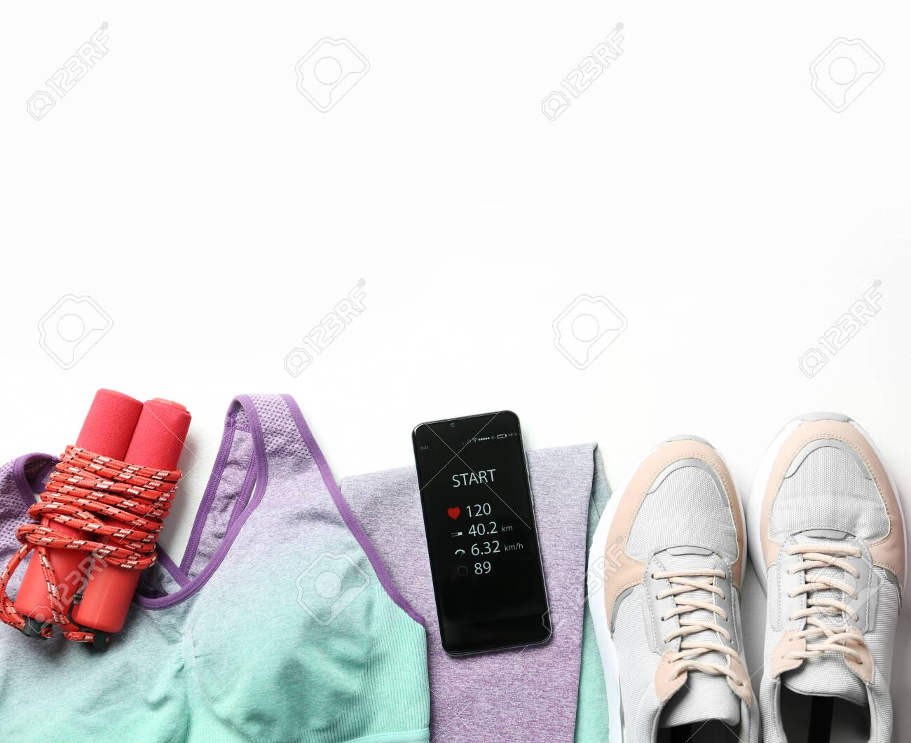 Smartphone with fitness app and sport accessories on white background, flat lay. Space for text - 144941375