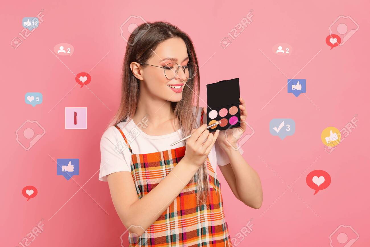 Beauty blogger with brush and eyeshadow palette on pink background - 145278986
