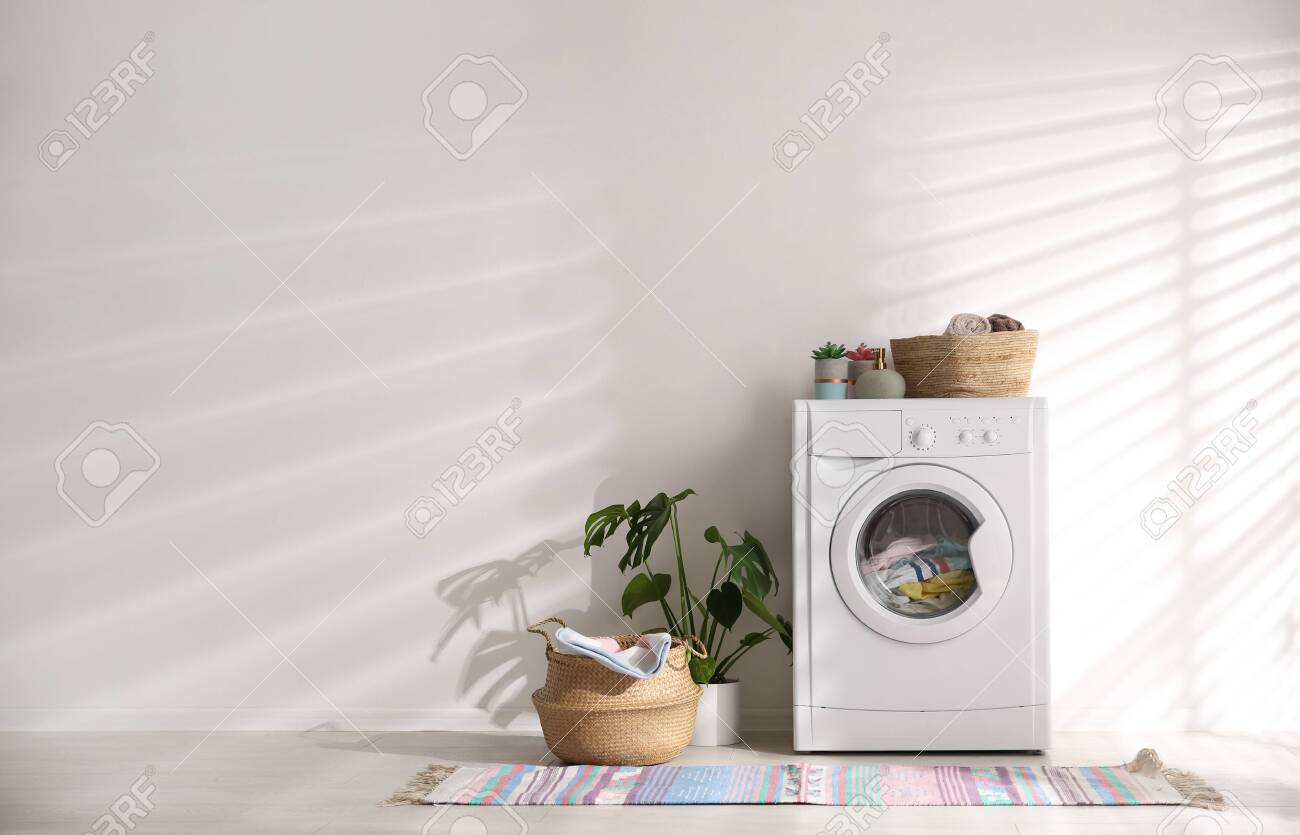 Modern washing machine and wicker basket with laundry near white wall, space for text. Interior design - 146369683