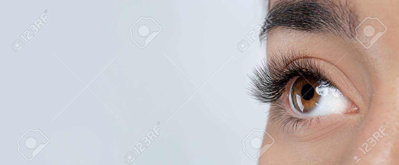 Closeup view of young woman with beautiful long eyelashes on grey background, space for text. Banner design - 147732517