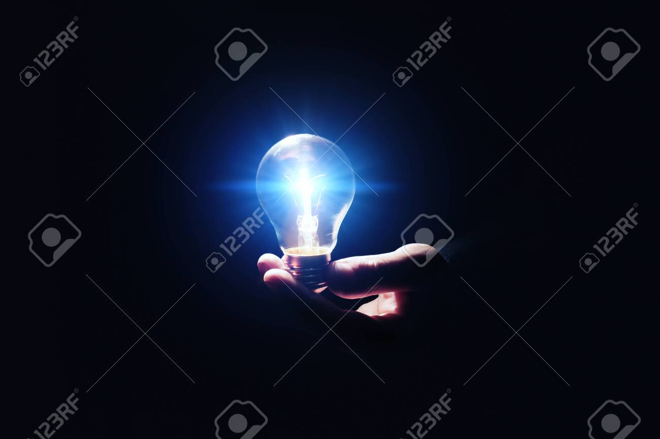Idea concept. Man with glowing light bulb in darkness, closeup - 147717625
