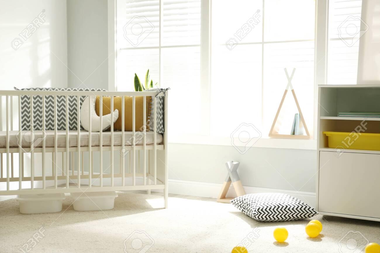 Cute baby room interior with crib and big window - 148585011