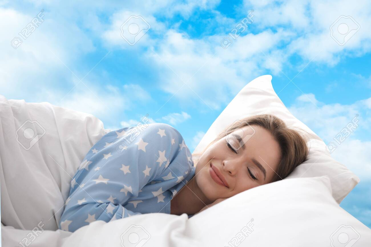 Young woman sleeping in bed. Blue sky on background - 148921141