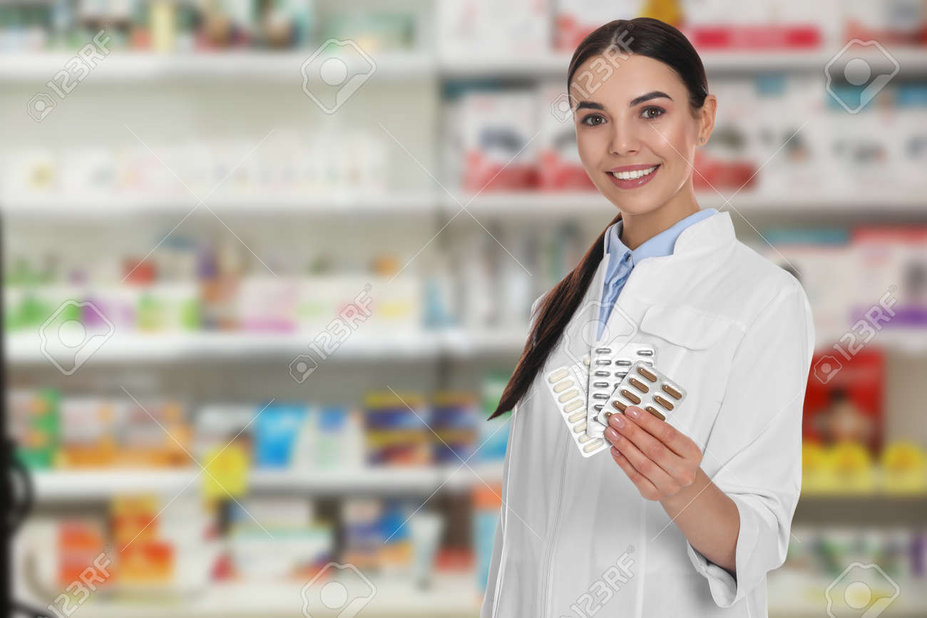 Professional pharmacist with pills in modern drugstore, space for text - 150136708