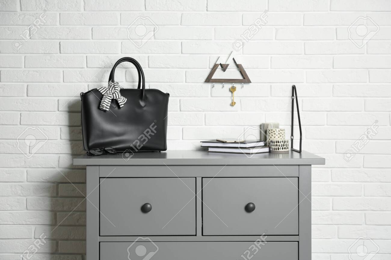 Grey Chest Of Drawers With Bag Books And Decor Elements Near Stock Photo Picture And Royalty Free Image Image 150006040