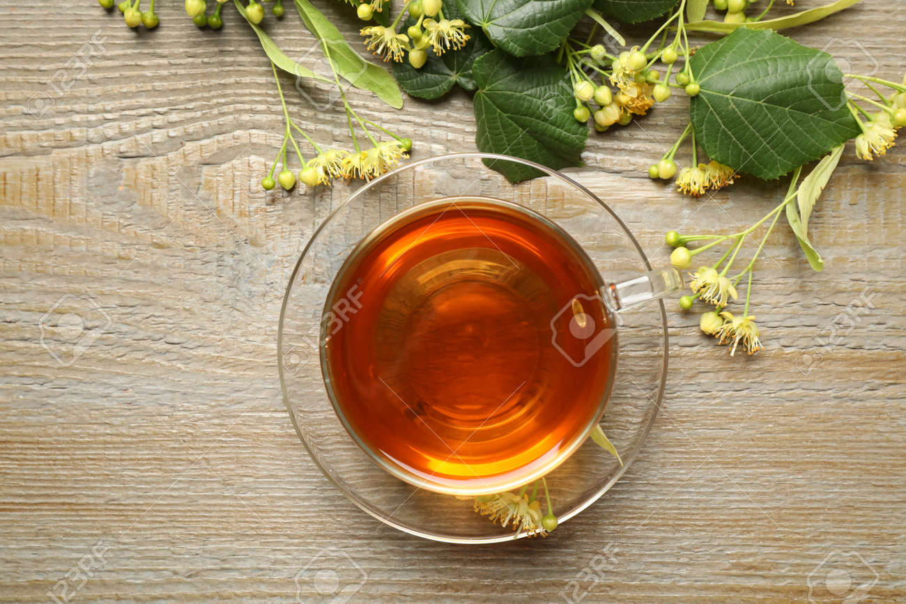Cup of tea and linden blossom on wooden table, flat lay - 150190767