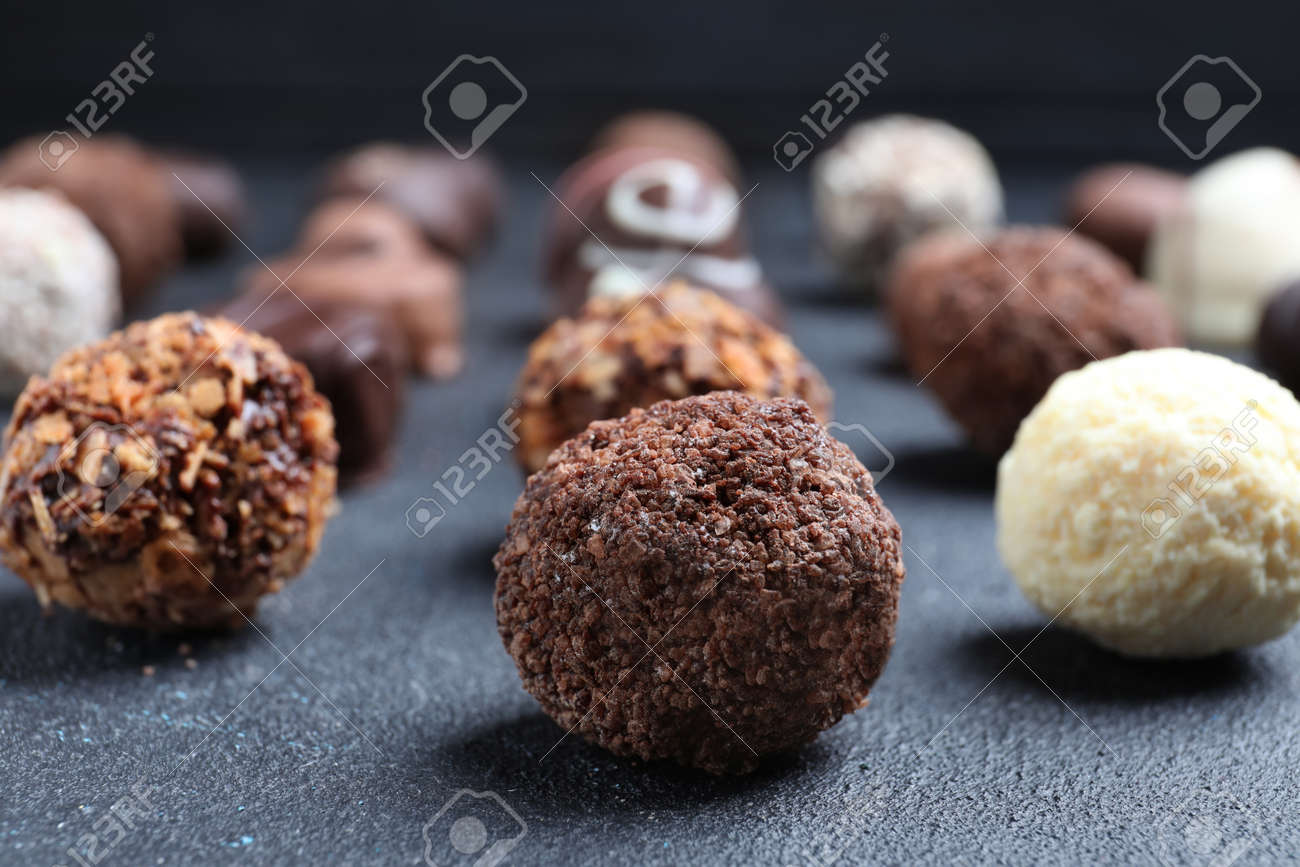 Different tasty chocolate candies on black table, closeup - 151003309