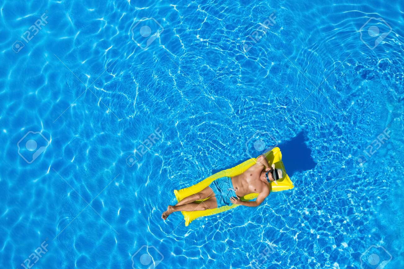 Young man with inflatable mattress in swimming pool, top view. Space for text - 154108051