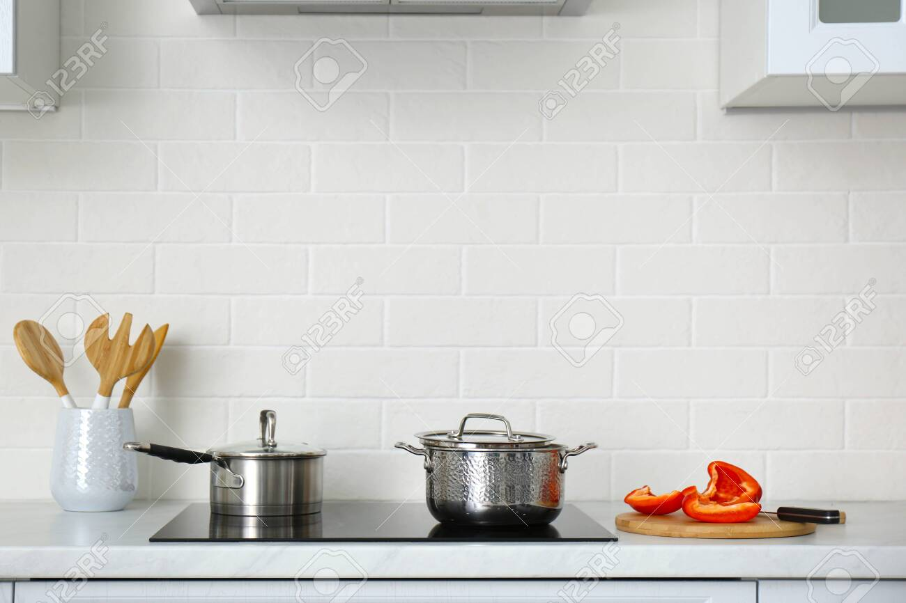 Kitchen counter with utensils and cookware on stove - 154173644