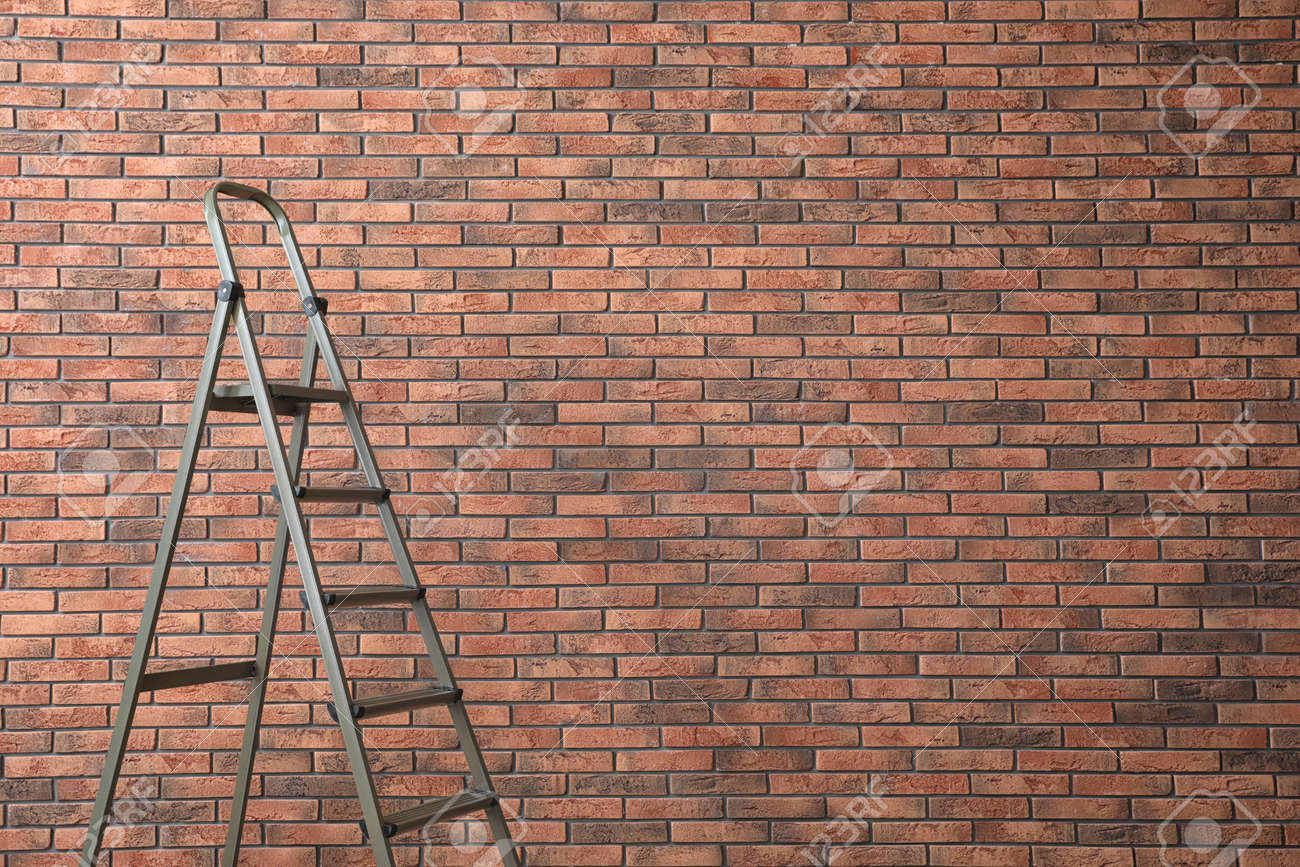 Metal stepladder near brick wall. Space for text - 154121836