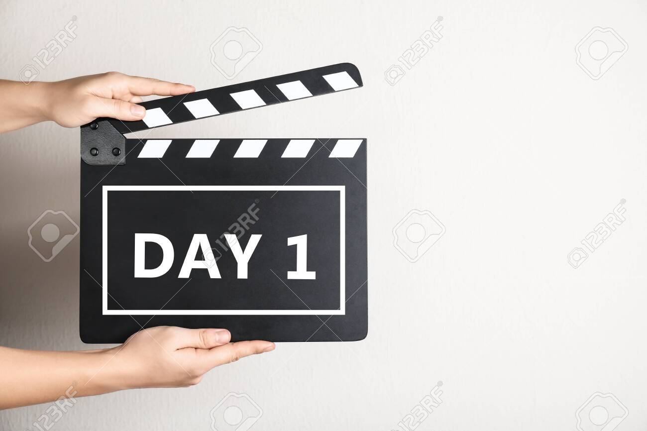 Starting new life chapter. Woman holding clapperboard with text Day 1, closeup - 154492807